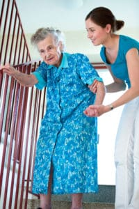 Senior woman is climbing stairs with home caregiver